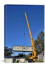 A caravan on the end of a crane hook