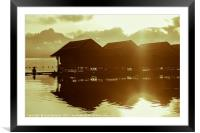 Sun rising over cute little wooden huts perched on, Framed Mounted Print